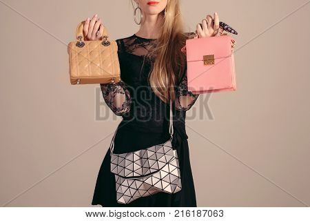 Young woman posing in black dress and three hand bag.