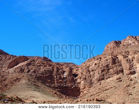 Rocky slope of TODGHA GORGE canyon landscape in MOROCCO, eastern part of High Atlas Mountains range at Dades Rivers near Tinghir town, clear blue sky in 2016 warm sunny winter day, Africa on February.