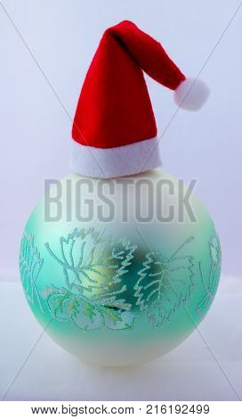 Christmas ball and cap from Santa Claus on gray background.