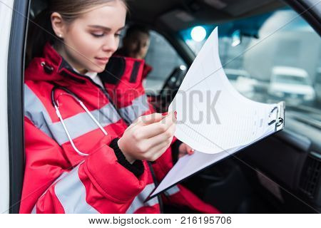 smiling paramedic sitting in ambulance and holding clipboard poster