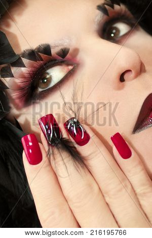 Black and red make-up with false eyelashes and long red nails with design of black feathers on female hand close up.