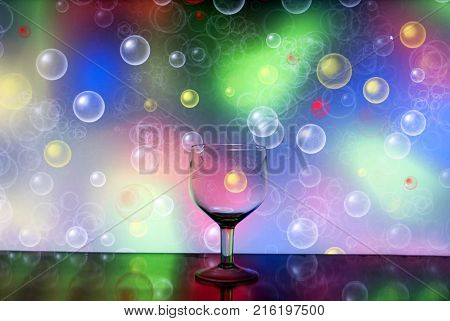 glass wine glass for drinking wine on a background with different colors of circles