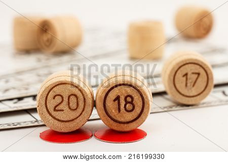 Wooden lotto barrels with numbers of 20 and 18 replace 17 as New Year 2018 is coming concept and game cards for a game in lotto on the background