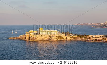 A casino at the entrance to St George's Bay in St Julian in Malta. Photo taken during the golden hour.