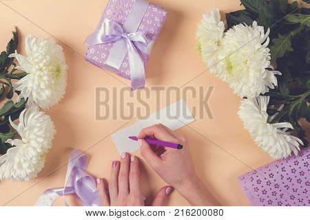 woman hand writing a note with the text thank you on a paper, over beige table and flowers. toned