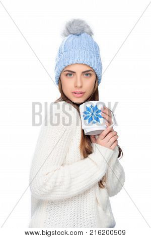 beautiful woman in knitted hat drinking coffee while sitting on stool isolated on white