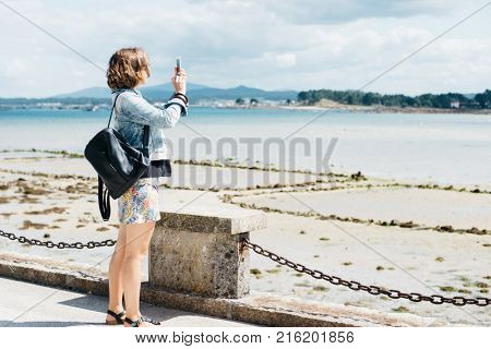 Young female tourist taking a photo on cellphone of the Atlantic ocean, O Grove, Galicia, Spain. Traveler standing on pier and taking photo of a coastline