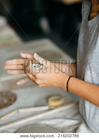 Closeup of female hands maker ceramics working with clay and creating a shape of ceramic objects. Pottery making.