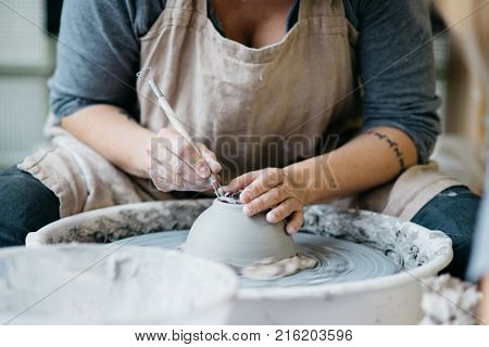 Ceramic working process with clay potter's wheel. Young woman making pottery in studio.