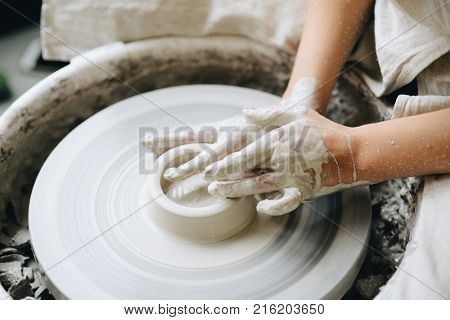 Ceramic working process with clay potter's wheel. Young woman making pottery in studio. Female hands on pottery wheel