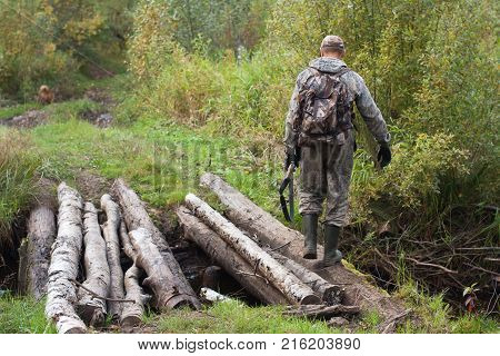 hunter with shotgun crossed the forest river on the bridge