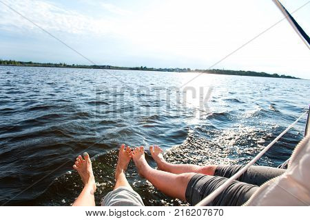 Two couples of funny woman's feet on shipboard sailing through the sea. Personal view point wide angle. Outdoors horizontal colored summertime image.