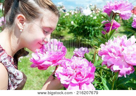 Pretty teenage girl smelling bouquet of pink rich blossoming Minuet peony flowers in sunny green park. Summertime multicolored outdoors horizontal image.