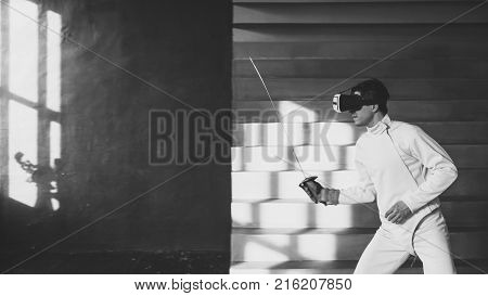 Concentrated young fencer man practice fencing exercises using VR headset and training simulator competition game indoors