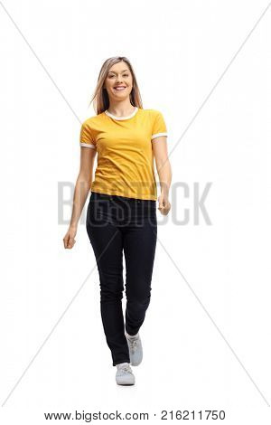 Full length portrait of a young woman walking towards the camera and smiling isolated on white background