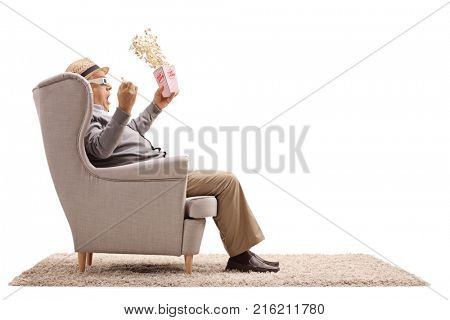 Terrified senior with a popcorn box and 3D glasses seated in an armchair isolated on white background