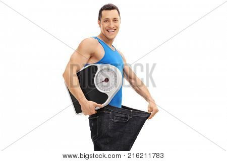Guy in an oversized pair of jeans holding a weight scale isolated on white background