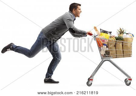 Full length profile shot of a guy running and pushing a shopping cart filled with groceries isolated on white background