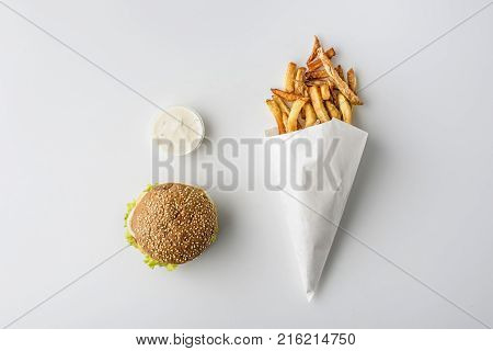 top view of hamburger and french fries in paper cone isolated on white