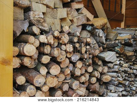 Chopped and sawn firewood for a stove in a bath. A woodpile near the house.