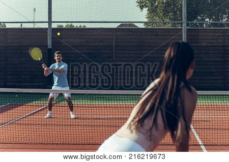 Catch it! Rear view of young couple playing tennis on the tennis court.