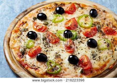 Pizza with mozzarella, black olives, jalapeno pepper and cherry tomatoes