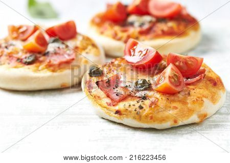 Home baked mini pizza topped with ham, cherry tomatoes and capers on wooden background