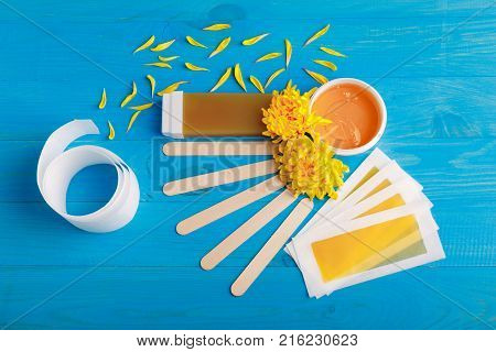 Set for depilation stripes, cassette with wax, chopsticks and lepidist chrysanthemums at the pot with wax on a blue wooden background