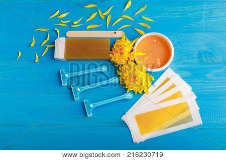 Set for depilation with strips, chopsticks, wax in a cup and wax in a cassette and a row of razors with chrysanthemums on a blue wooden background