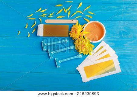 Set for depilation with strips, chopsticks, wax in a cup and wax in a cassette and a row of razors with chrysanthemums on a blue wooden background. View from above