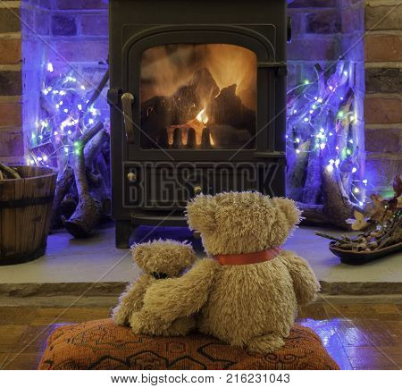 Two teddy bears waiting for Santa Claus in front of a log fire.