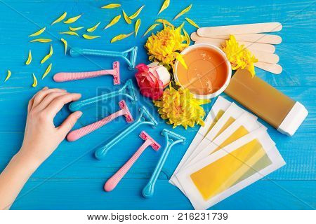 Set for depilation with strips, the hand touches razors with colored, wax, chopsticks and cassette with wax on a blue wooden background. Top view of a closeup
