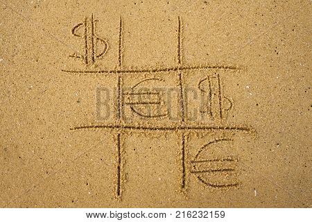 Tic-tac-toe game with playing euro and dollar symbols on sand. Concept of financial currency games