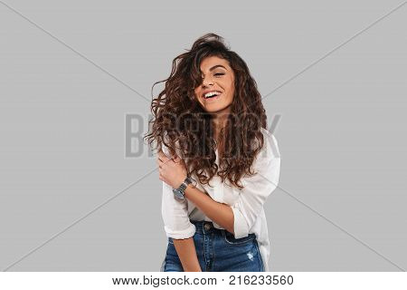 Pure beauty. Attractive young woman smiling while standing against grey background
