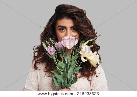 Beautiful as a flower. Attractive young woman covering face with bunch of flowers and looking at camera while standing against grey background