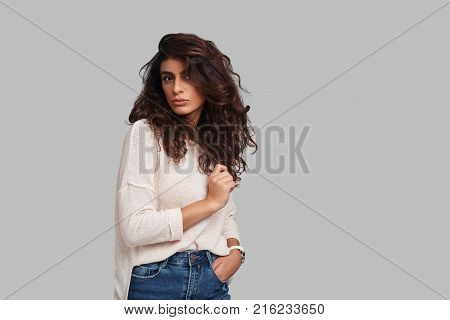 Charming girl. Attractive young woman looking at camera and keeping hand in pocket while standing against grey background