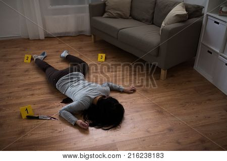 murder, kill and people concept - dead woman body and knife in blood lying on floor at crime scene (staged photo)