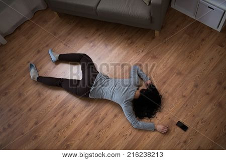 murder, kill and people concept - unconscious or dead woman body and smartphone lying on floor at crime scene (staged photo)