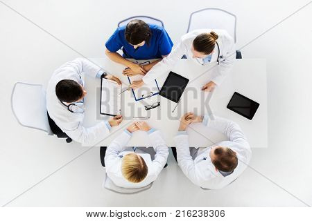 medicine, healthcare and cardiology concept - group of doctors with cardiograms, clipboard and tablet pc computers at hospital