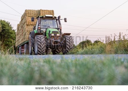 Green Tractor With A Yellow Barrel Sprays Substances Into Vegetable Beds