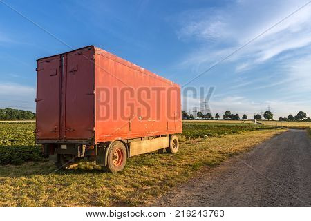 Red, closed agricultural trailer on the left side of a field