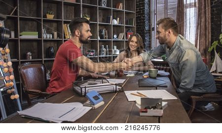 Beginning of cooperation. Startup business team with men and young business woman sitting in office with businessmen partner who shaking hands with young man and congratulates him with starting work