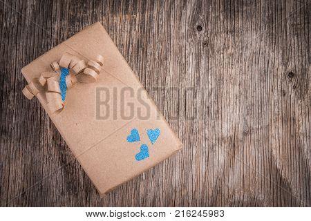Handmade cardbord gift box on wooden vintage background