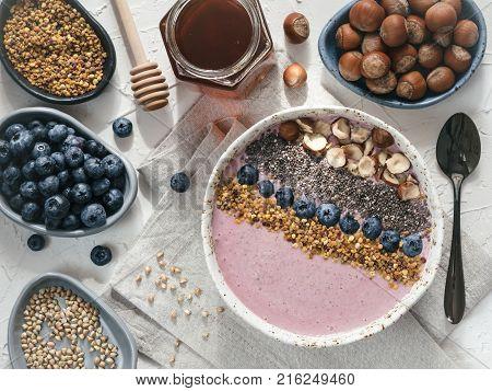 Healthy breakfast. Buckwheat Porridge. Raw buckwheat vegan breakfast smoothie bowl with fresh blueberry nuts chia seeds and bee pollen. Clean eating dieting detox vegetarian food concept. Topview