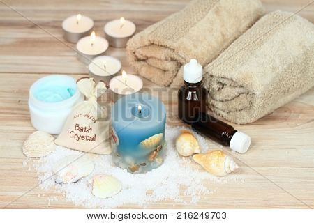 Aromatherapy spa concept with candles . Aromatherapy treatment aromatic oil bath crystals seashells cream and decoration on wooden background