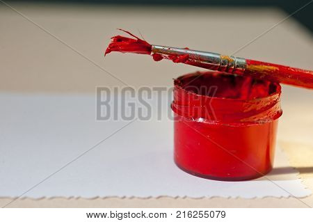 A jar with red paint and a brush on a sheet of white paper
