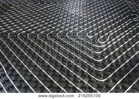Radiant underfloor heating installation with flexible tubing mounted on insulation boards