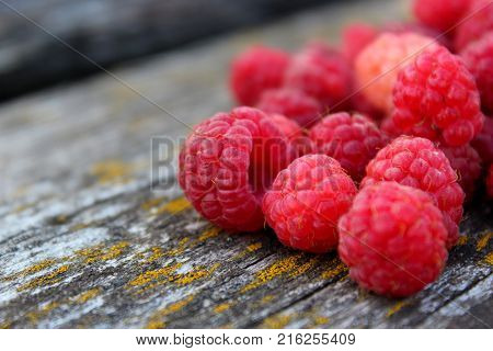 Fresh raspberry. Ripe raspberry on the table in the garden. Juicy red berries on a wooden table. Delicious and healthy food. A healthy way of life. Sweet raspberry. Jam of raspberries. Summer berry