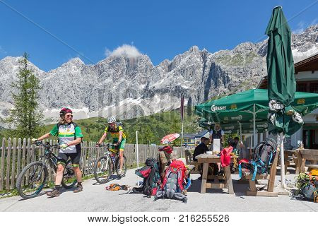 DACHSTEIN MOUNTAINS, AUSTRIA - JULY 17, 2017: Man and woman with mountain bike and alpinists equipment for rock-climbing in Dachstein Mountains of Austria