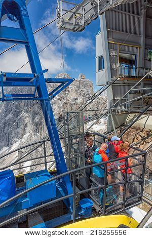 DACHSTEIN MOUNTAINS, AUSTRIA - JULY 17, 2017: Cable car approaching the Dachstein glacier mountain station in Austria. Some people are standing at the balcony at the roof of the cable car